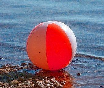 Mit einem aufblasbaren Wasserball am Strand spielen